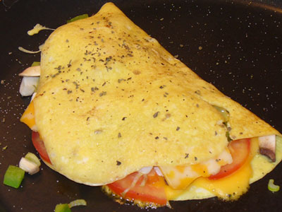 Omelette with cheese and slices of tomato.