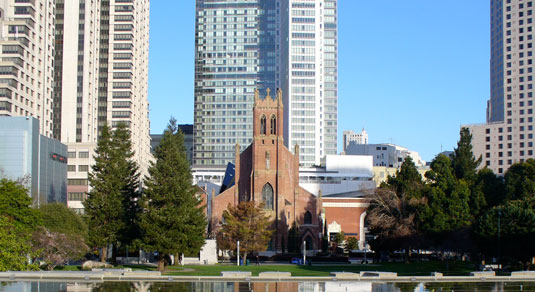 Red stone church near green trees, surrounded by skyscrapers.