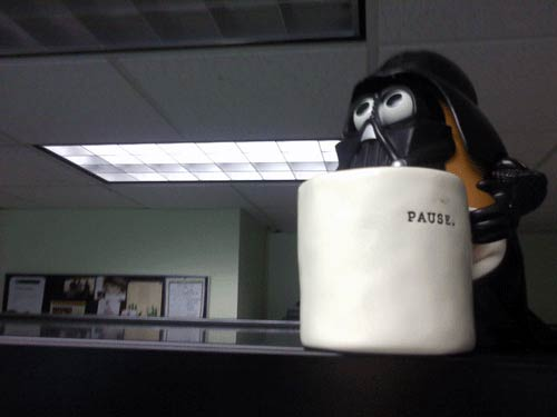 "The ""Pause."" cup in front of a Vader figurine."