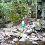 Lila standing on rocky riverbank.