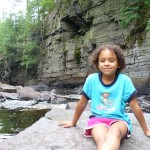 Eva sitting on rock in river