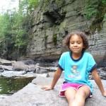 Eva sitting on rock in river