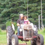 Eva getting a tractor ride from uncle A.J.