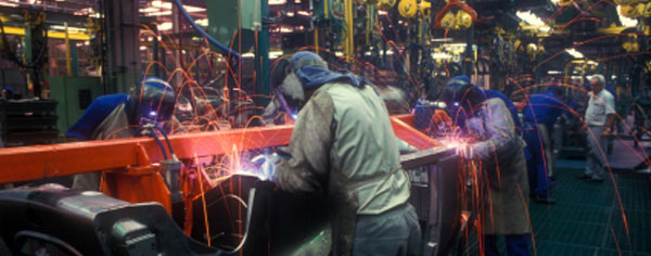 Workers welding on an automobile assembly line.