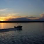 A fishing boat heading home at dusk.
