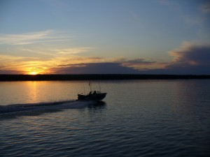 A fishing boat heading home at dusk.