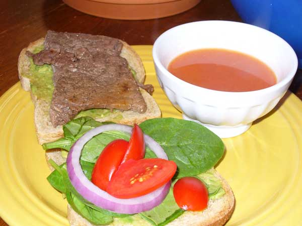 Steak, spinach, onion, tomato, and avacado sandwich, with bowl of tomato soup.