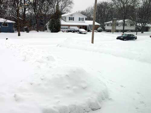 Snowy street and snowbanks along driveways